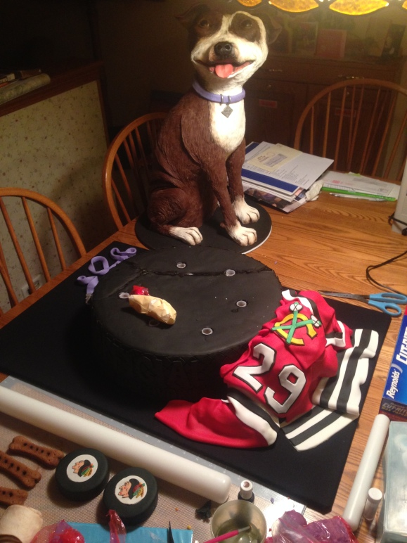 life sized dog cake with blackhawks gear and gigantic puck