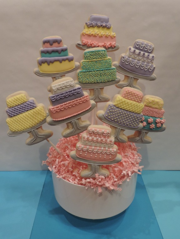 bunch of tiered cake cookies decorated with royal icing
