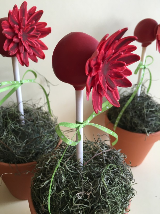 red flowers on cake pops from side